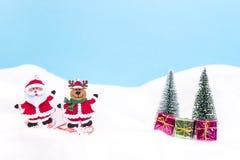 En Santa Claus och en ren med gåvor Arkivfoto