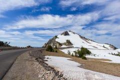 En scenisk huvudväg Rim Drive med den väktarePeak för stenigt berg bakgrunden i krater sjönationalpark arkivbild