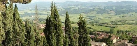 En scenisk sikt av en Tuscan dal med träd i förgrunden arkivbild