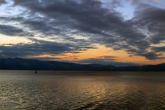 En scenisk solnedgång med ett svart moln ovanför det sista solskenet reflekterat i Ohrid sjön, Makedonien royaltyfri foto