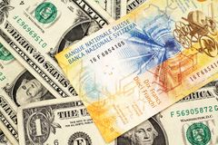En schweizisk francsedel med amerikanen en dollar räkningar royaltyfri bild