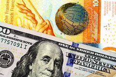 En schweizisk francsedel med en amerikansk hundra dollarräkning fotografering för bildbyråer