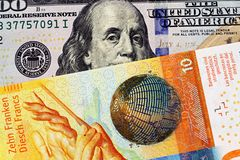 En schweizisk francsedel med en amerikansk hundra dollarräkning arkivbild