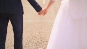 En se donnant la main des jeunes mariés soyez sur la route tenant des mains banque de vidéos