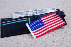 En sedel hundra dollar, svart handväska och en amerikanska flaggan Arkivfoton