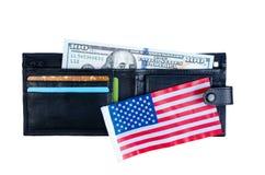 En sedel hundra dollar, svart handväska och en amerikanska flaggan Royaltyfri Foto