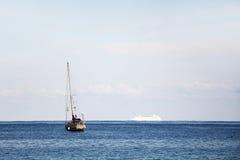 En segelbåt och ett kryssningskepp i havet Arkivbilder