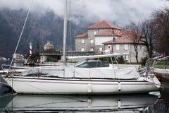 En segelbåt på pir, ett stenhus på kusten och en fyr i fjärden Berg i dimma royaltyfri foto