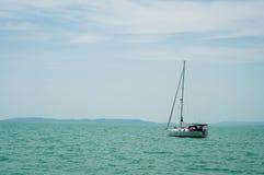 En segelbåt väntar i daglugn under härlig blå himmel med moln på sjön Balaton, Ungern Berg på bakgrund Yac Royaltyfri Bild