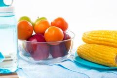En selectivo del cuenco de fruta con la manzana roja, la manzana y la naranja verdes pusieron al lado de plato borroso del maíz a fotografía de archivo libre de regalías