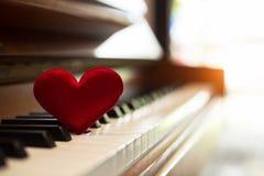 En selectivo del pequeño corazón rojo ponga el piano encendido borroso, tono ligero caliente del vintage fotos de archivo libres de regalías