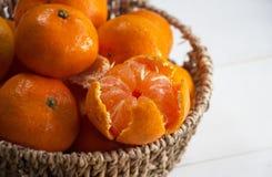 En selectivo Peeled la naranja puso en cesta tejida, al lado del grupo de naranjas borrosas imagen de archivo