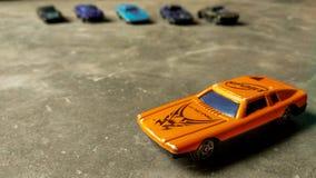 En selektiv fokuserad billeksak Closeup av den orange leksakbilen f?r barn p? olik bakgrund royaltyfri foto
