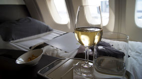 EN SEPTIEMBRE DE 2014: Primera clase que cena a bordo de Boeing 747, del vino blanco, del agua y de las nueces Foto de archivo libre de regalías