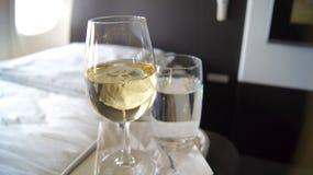 EN SEPTIEMBRE DE 2014: Primera clase que cena a bordo de Boeing 747, del vino blanco y del agua Fotos de archivo