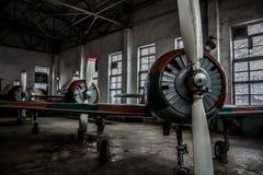 En serie av brutet gammalt sportflygplan i en hangar Royaltyfri Fotografi