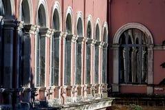 En serie av fönster reflekterade på ett annat fönster En 19th byggnads för århundradeneo-renässans stil borggård med välvda fönst royaltyfria foton