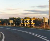 En serie av tecken varnar chaufförer av en skarp krökning i UK royaltyfri fotografi