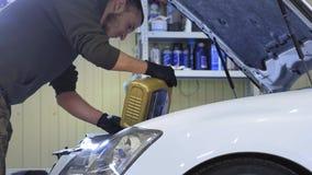 En servicearbetare häller syntetisk olja in i en passagerarebil inom en servicestation stock video