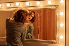 En sexig flicka med flödande brunt hår i en stucken tröjapassion som poserar nära spegeln med, modefoto fotografering för bildbyråer