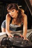 En sexig kvinna som reparerar en engion av en bil royaltyfria bilder