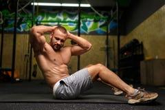 En sexig man som gör en övning på ett golv och på en bakgrund av en idrottshall Sport-, utbildnings- och övningsbegrepp Arkivbilder