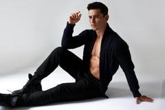 En sexig muskulös modell för ung man, på den nakna torson i svart som sitter i studio, på vit bakgrund arkivfoton