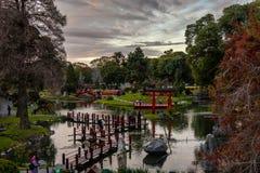 En Shinto relikskrin, en bro och en bana i en japansk trädgård royaltyfria foton