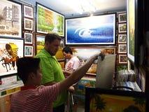En shoppare väljer från en variation av till salu målningar arkivbild
