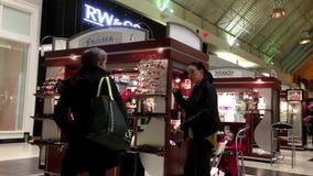 En sida av folk som shoppar och pratar med arbetaren lager videofilmer