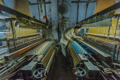 En siden- tillverkare undersöker hans arbete på en liten fabrik i Varanasi, Indien Royaltyfria Foton