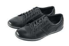 En sidosikt av ett par av skor för svart man` s för sportar Arkivfoton