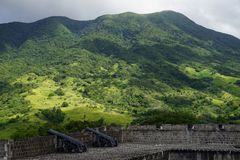 En sikt över kullar för St Kitts med befästningar för svavelkullefästning på förgrunden på en ljus solig dag Fotografering för Bildbyråer
