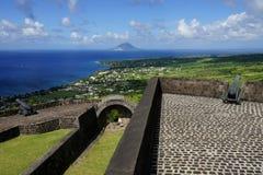 En sikt över St Kitts och Sint Eustatius öar med befästningar för svavelkullefästning på förgrunden på ett ljust soligt Arkivbilder
