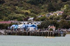 En sikt av Akaroa, Nya Zeeland från havet med kryssningfartygpassagerare som tycker om staden arkivfoto