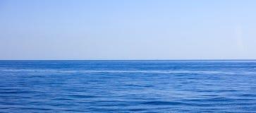 En sikt av bakgrund för lugna hav och för blå himmel, Fotografering för Bildbyråer