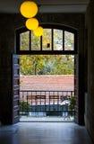 En sikt av en balkong på slutet av korridoren med bollen formade lampor och järnverk royaltyfri bild