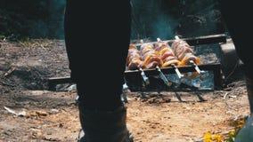 En sikt av benen av en manmatlagningkebab på steknålar över en brand i bygden i byn lager videofilmer