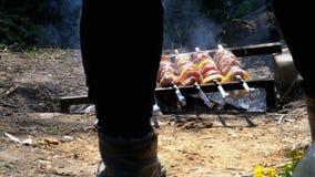 En sikt av benen av en manmatlagningkebab på steknålar över en brand i bygden i byn stock video