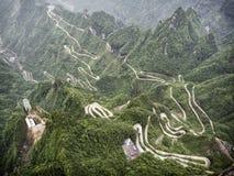 En sikt av de farliga 99 kurvorna på den Tongtian vägen till det Tianmen berget, porten för himmel` s på Zhangjiagie, Hunan lands Arkivfoton