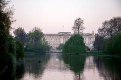 En sikt av den Buckingham Palace- och för drottningen Victoria minnesmärken från St James ` s parkerar sjön i ottan, London Arkivfoton
