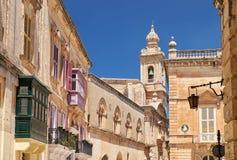 En sikt av den gamla Mdina gatan med det Carmelite kyrkliga Klocka tornet på t Arkivbild