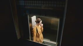 En sikt av den unga attraktiva upptagna Caucasian kvinnan som rider upp i en genomskinlig glass hiss i en stor kontorsbyggnad lager videofilmer