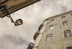 En sikt av en belagd med tegel byggnad och en lampa mot en molnig himmel, Lissabon, Portugal royaltyfri bild