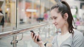 En sikt av en flicka från en sidovinkel Hon sitter i ett offentligt ställe, genom att använda hennes telefon som ler lager videofilmer