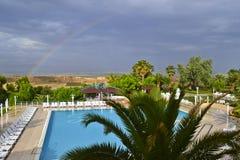 En sikt av ett lantlig landskap, simbassäng och regnbåge arkivbilder