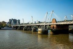 En sikt av femtioårsjubileum- och Hungerford broar från den södra banken av Thames River i London Arkivbilder