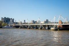 En sikt av femtioårsjubileum- och Hungerford broar från den södra banken av Thames River i London Royaltyfri Fotografi