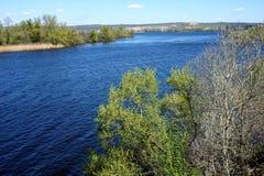En sikt av floden med mörker - blått vatten från en brant bank royaltyfria foton