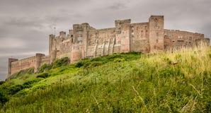 En sikt av en forntida slott överst av en gräskulle royaltyfri bild
